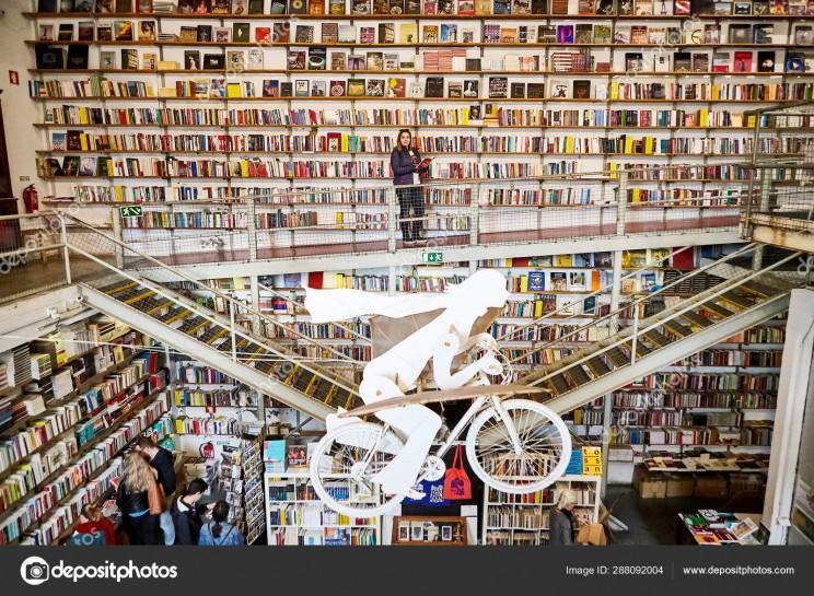 "LISBON, PORTUGAL - 12 of December 2018 - Woman tourist in Bookshop ""Livraria Ler Devagar"" in the LX factory"