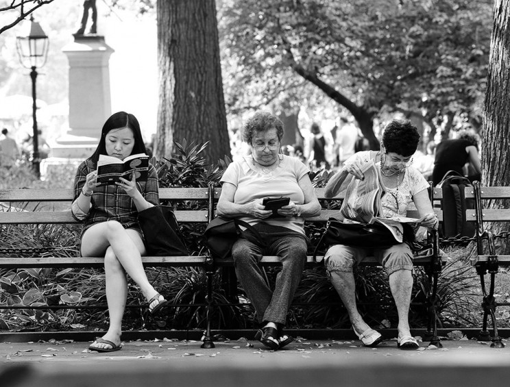 Reading Series--three women reading on a park bench in Washington square Park, October 4, 2013. exclusive photos by Lawrence Schwartzwald